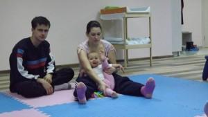 Проходило момченце прави упражненията заедно с мама и тати