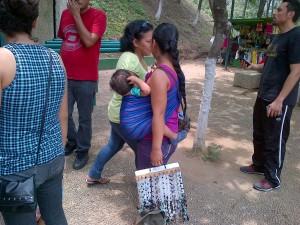 Майка с дете  продава мънистени огърлици на улицата