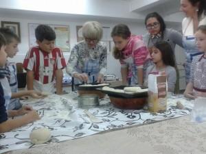 Майсторката на просфори, Диана, показва на децата от неделното училище как се месят и оформят отделните питки